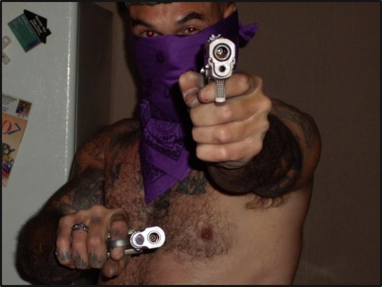 Steven Walter Cooke of the Aryan Brotherhood holding a gun.