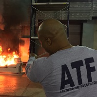 ATF fire researcher watch flames engulf a couch.