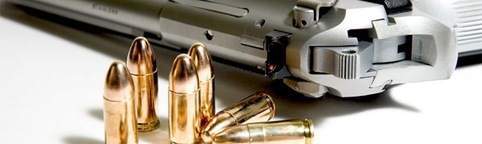 Image of bullets and a gun on a table