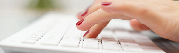 Image of a pair of hands using a computer keyboard