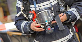 Image of a fire investigator holding equipment