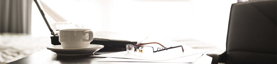 Image of a laptop, newspaper and a pair of glasses