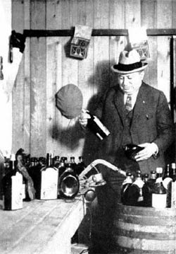 Image of Prohibition Agent Number One examines some whiskey bottle labels in South Brooklyn