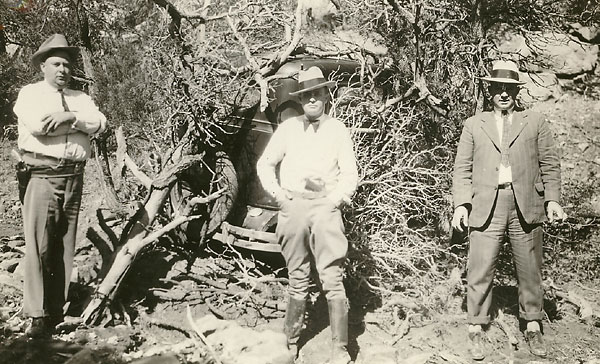 Picture of three searchers posing in front of Sutton's sedan hidden under brush.