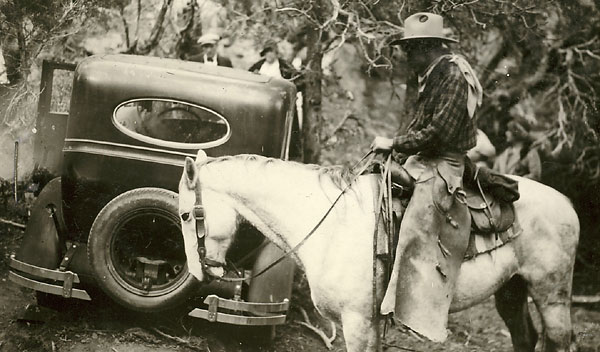 Image of a search volunteer on horseback examining Ray Sutton's abondened car and crime scene.