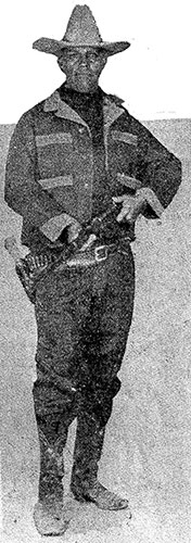 Full Image of Tom Threepersons holding a rifle and carrying a holstered pistol.