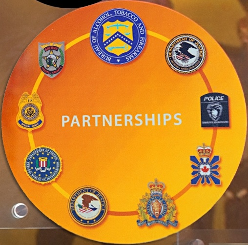 Image of the seals and badges of the ATF, INS, Charlotte-Mecklenburg Police, Canadian Security Intelligence Service, Royal Canadian Mounted Police, DOJ, FBI, Diplomatic Security, and Iredell County Sheriff, who were all involved in the investigation.