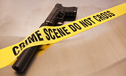 Image of a gun with a supressor and crime scene tape