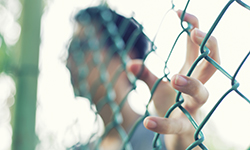 Image of a youth holding a fence