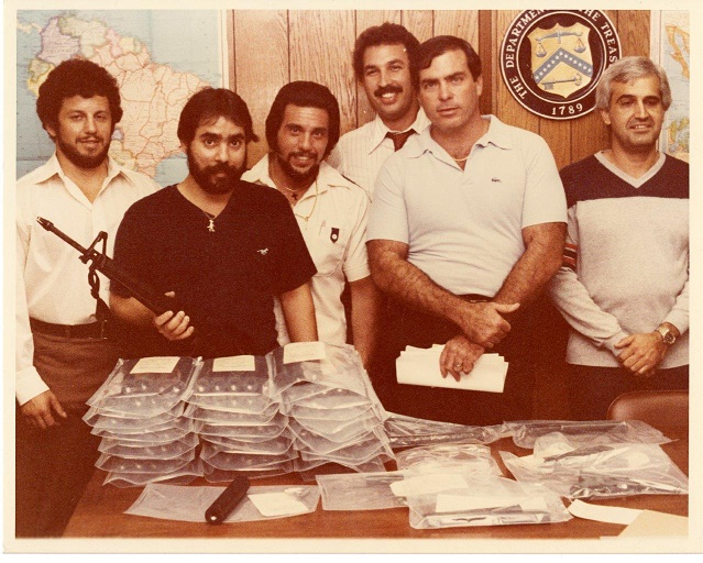 Image of Special Agent Ariel Rios and other special agents posing next to seized evidence.