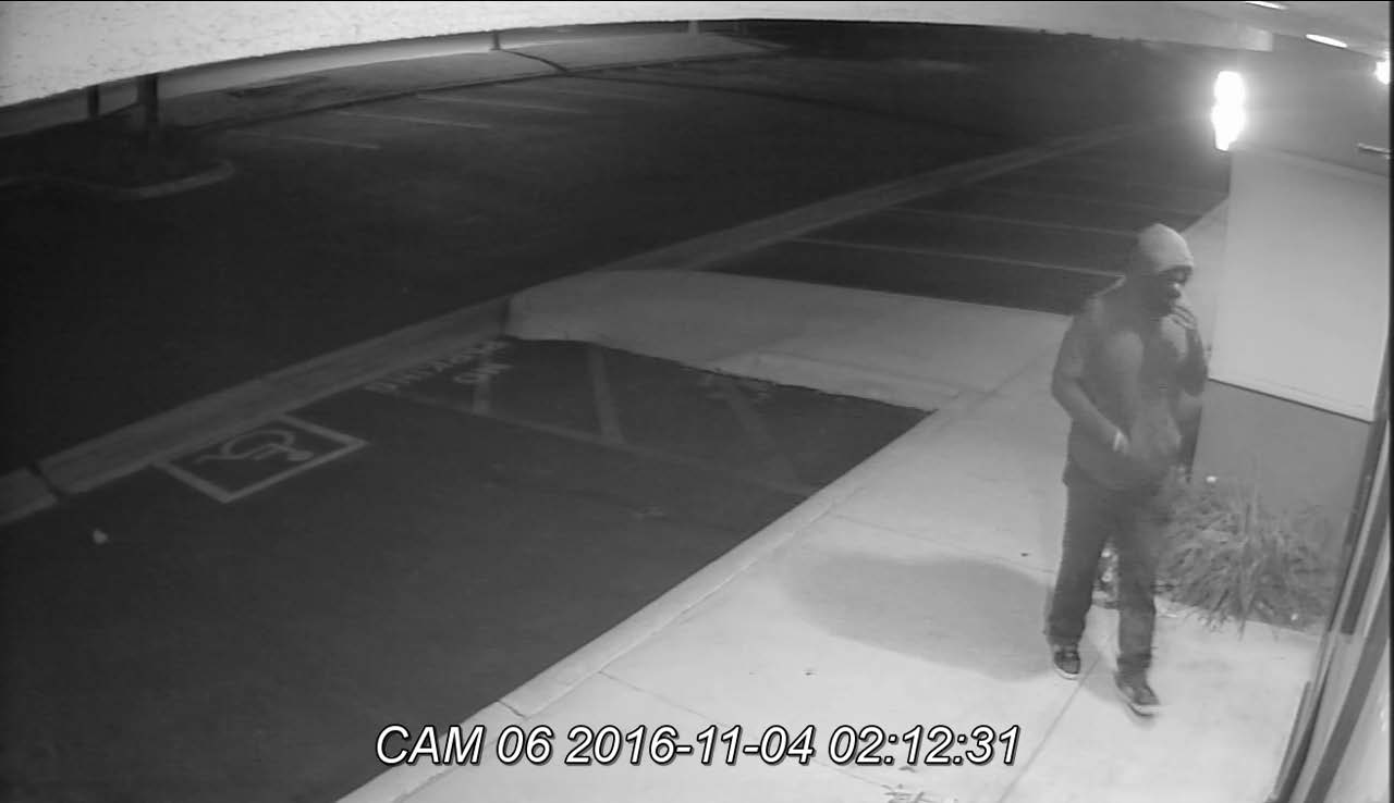 Image of a hooded suspect walking up to the store.