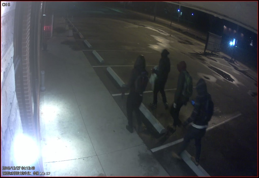 Image of four people wear jackets with the hoods over their heads walking through a parking lot. Three of the four are also wearing backpacks.