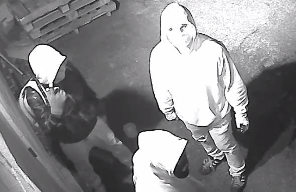 Image of 3 suspects; one with a black jacket and a hood on, wearing a light bookbag; two wearing light hoodies with face masks on.