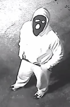Image of suspect 3 wearing a light hoodie, sweat pants, and a dark colored face mask.