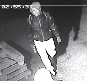 Image of suspect 1 ,wearing a dark jacket and a face mask.