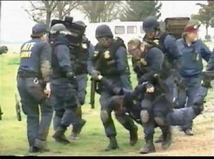 Four ATF agents move an injured agent to receive medical attention.