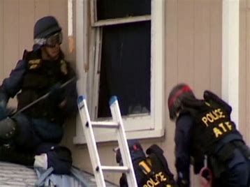 Image of ATF agents standing by an open window