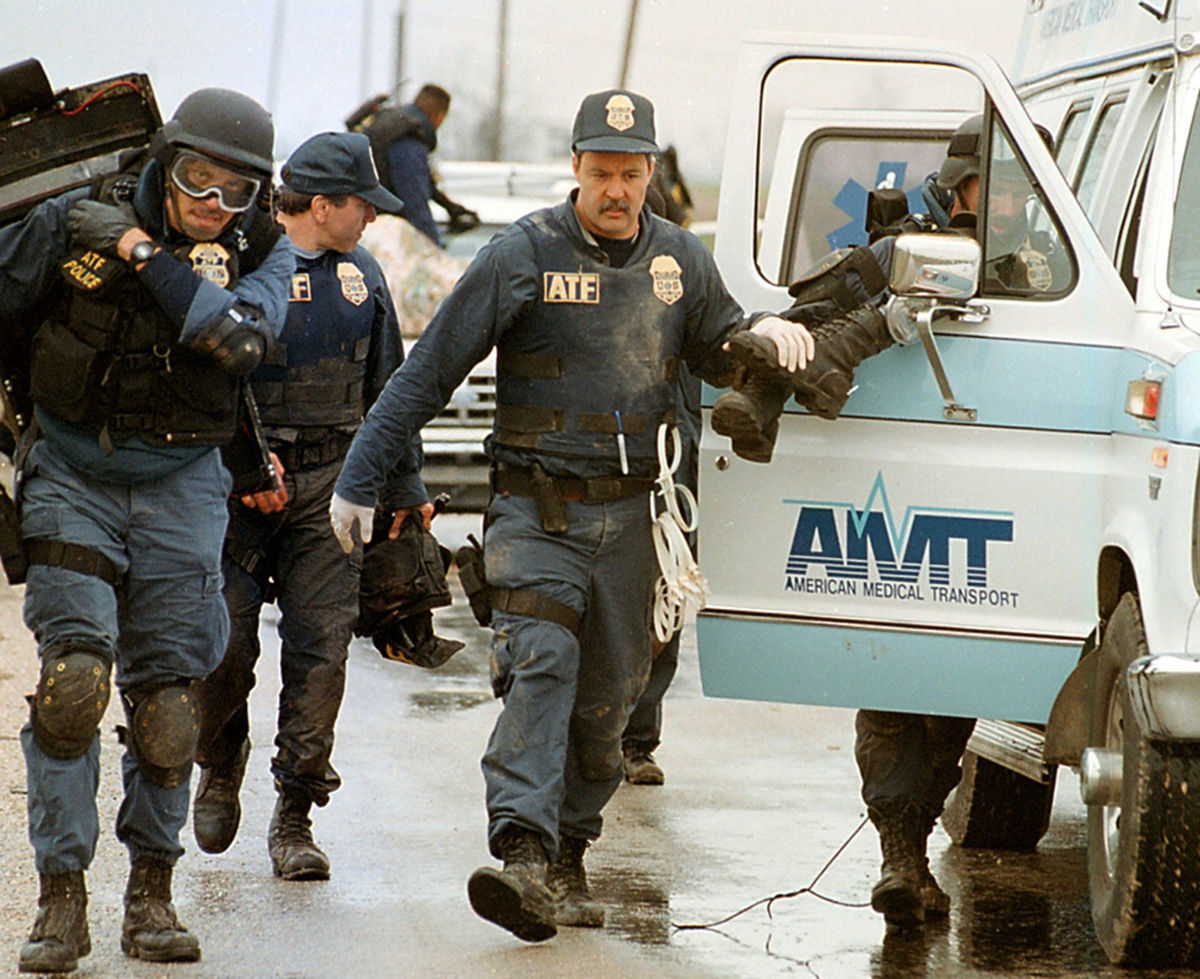 ATF agents help a wounded agent in a local ambulance.