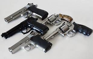Image of five handguns lying on a table.