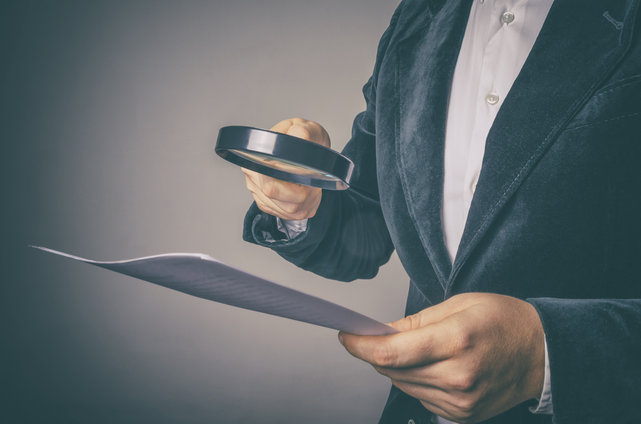 Image of a person holding a document in their hand with a magnifying glass