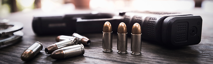 Image of a handgun with bullets on a wooden table