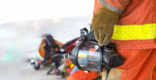 A firefighter in uniform holding a gas mask