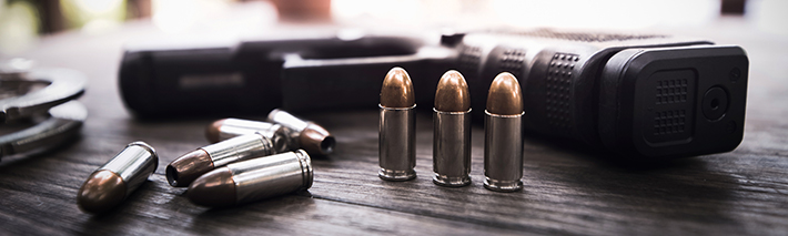 Image of bullets and a gun on a wooden table