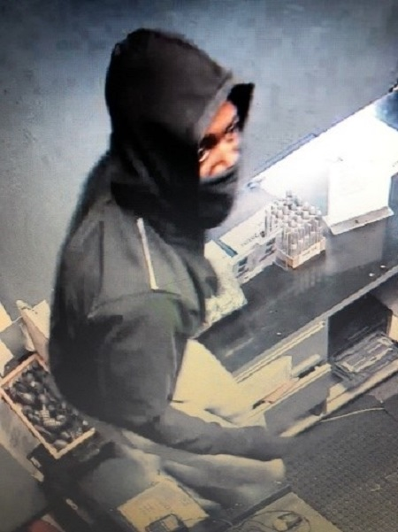 Wanted suspect wearing a dark hoodie and a dark face mask, covering the lower half of his face