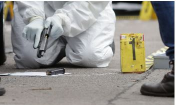 A forensics specialist recovers a firearm and bullets from a crime scene