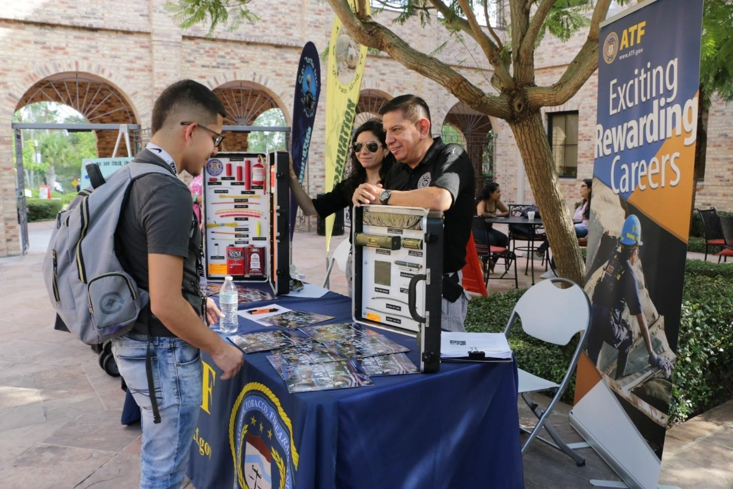 Industry Operations Investigator Edward working a recruiting booth at a local community college.