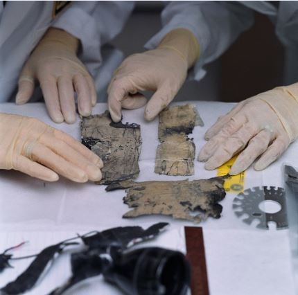 A forensic specialist examines fragments of an exploded pipe bomb