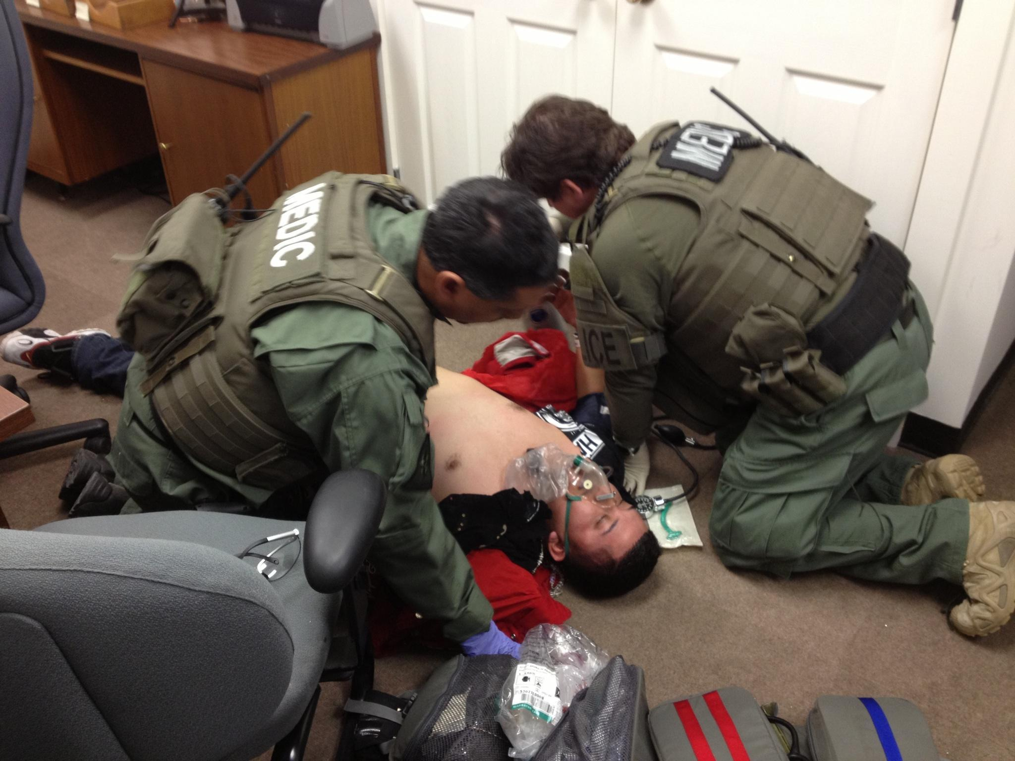 atf medics treat an injured suspect during a special response team arrest operation