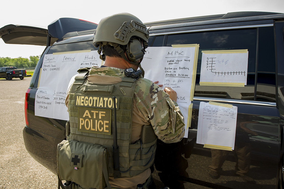 An ATF crisis negotiator drafts up a situation board to manage a crisis