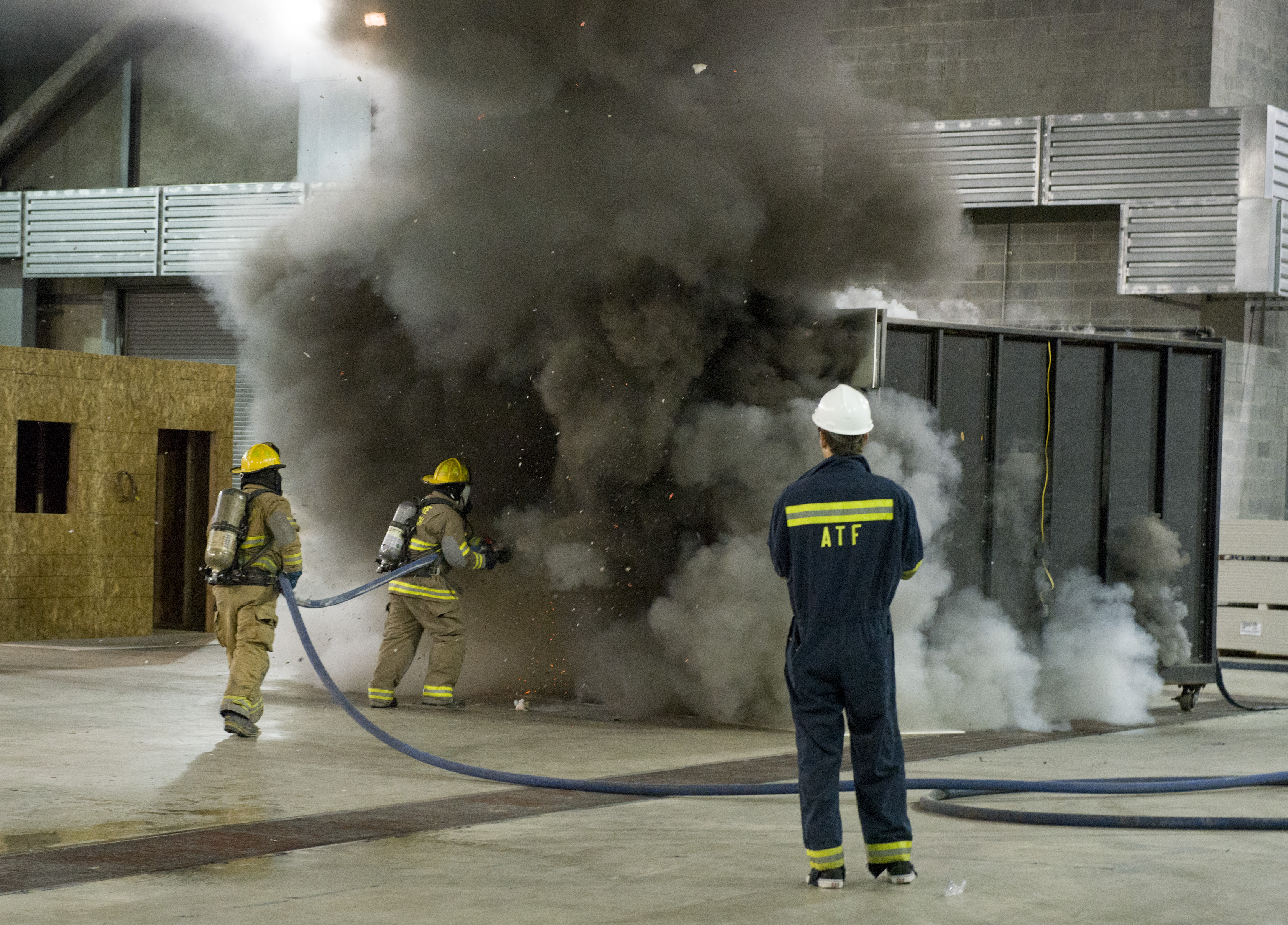 Two firemen use their hoses to extinguish a fire overseen by an ATF instructor.