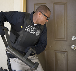 A special agent uses a breaching tool during a training scenario