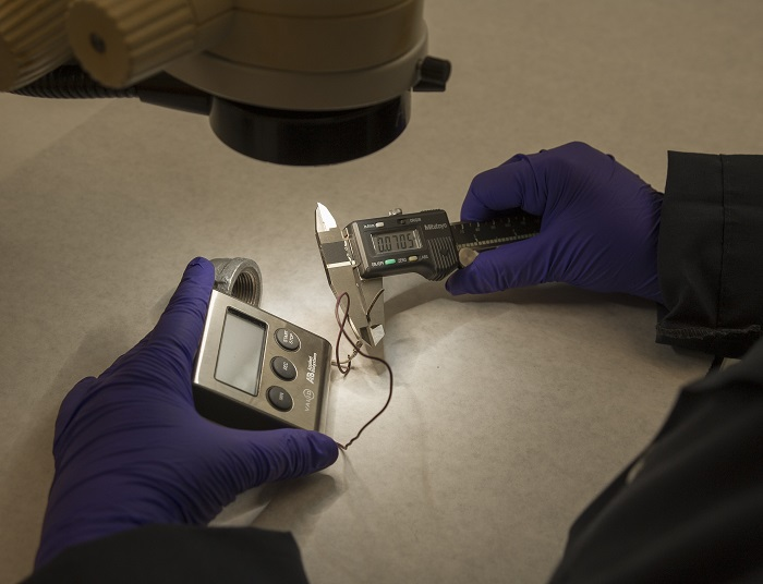 An examiner analyzes a piece of possible evidence in the laboratory.