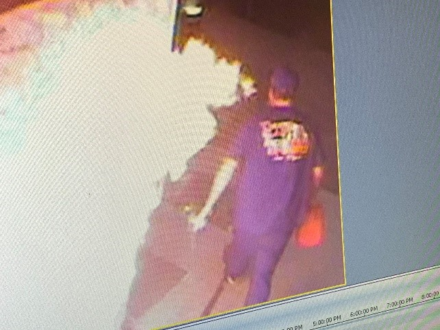 Security footage of arson suspect walking away from a fire with a gas can.