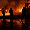 Burning building with firemen responding