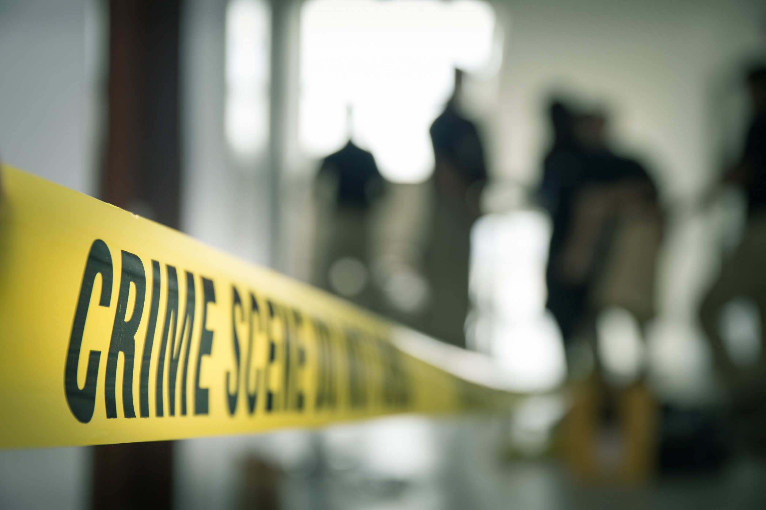 crime scene tape with blurred forensic law enforcement background in cinematic tone and copy space.