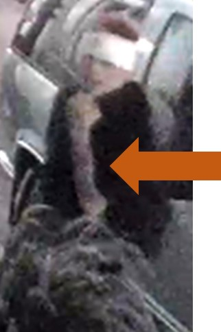 Person of interest wearing a dark top, white cloth wrapped are their head, carrying a bag, leaning against a vehicle.