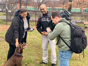 Special Agent Canine Handler George Goodman and K-9 Bonny are interviewed by the press
