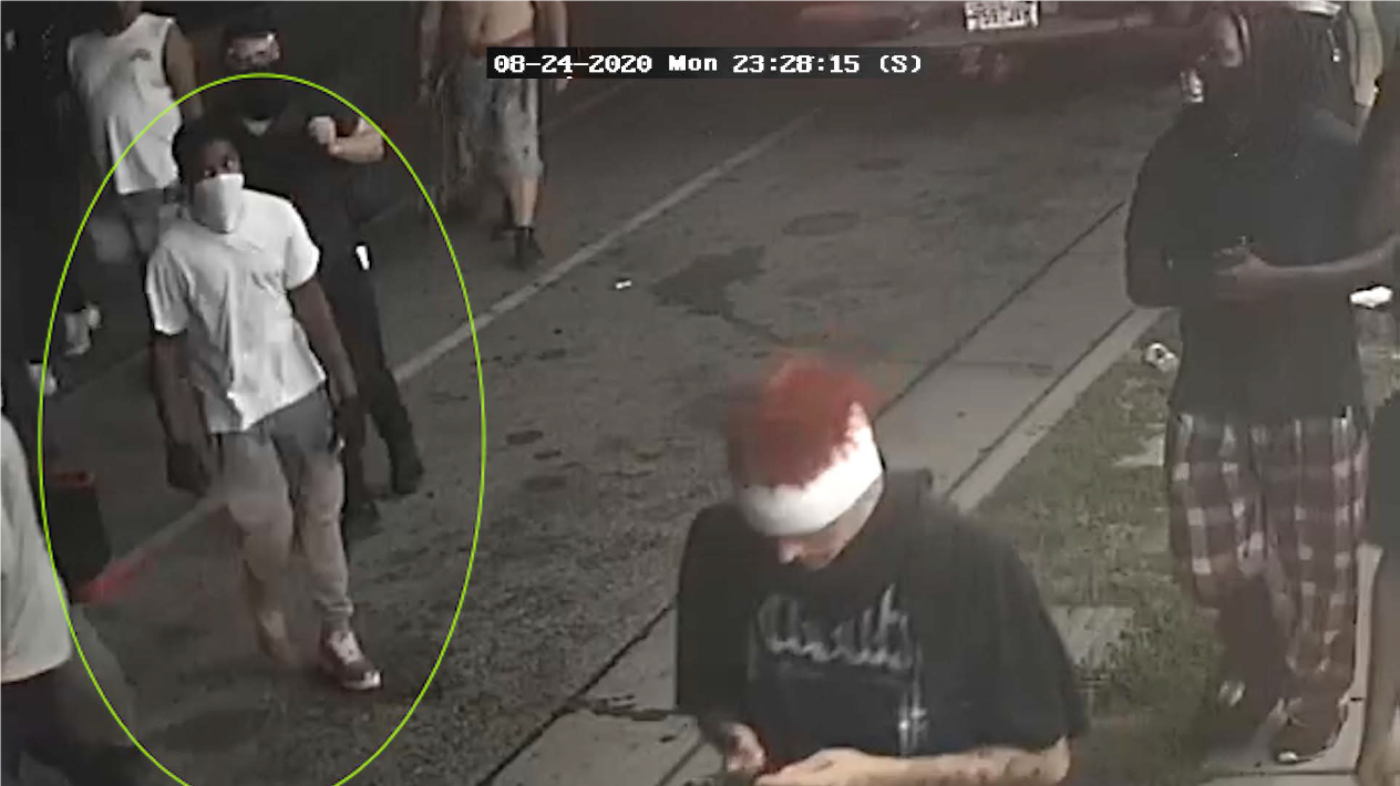 Male in white shirt and tan pants with a white face covering, identified as UNSUB #32.