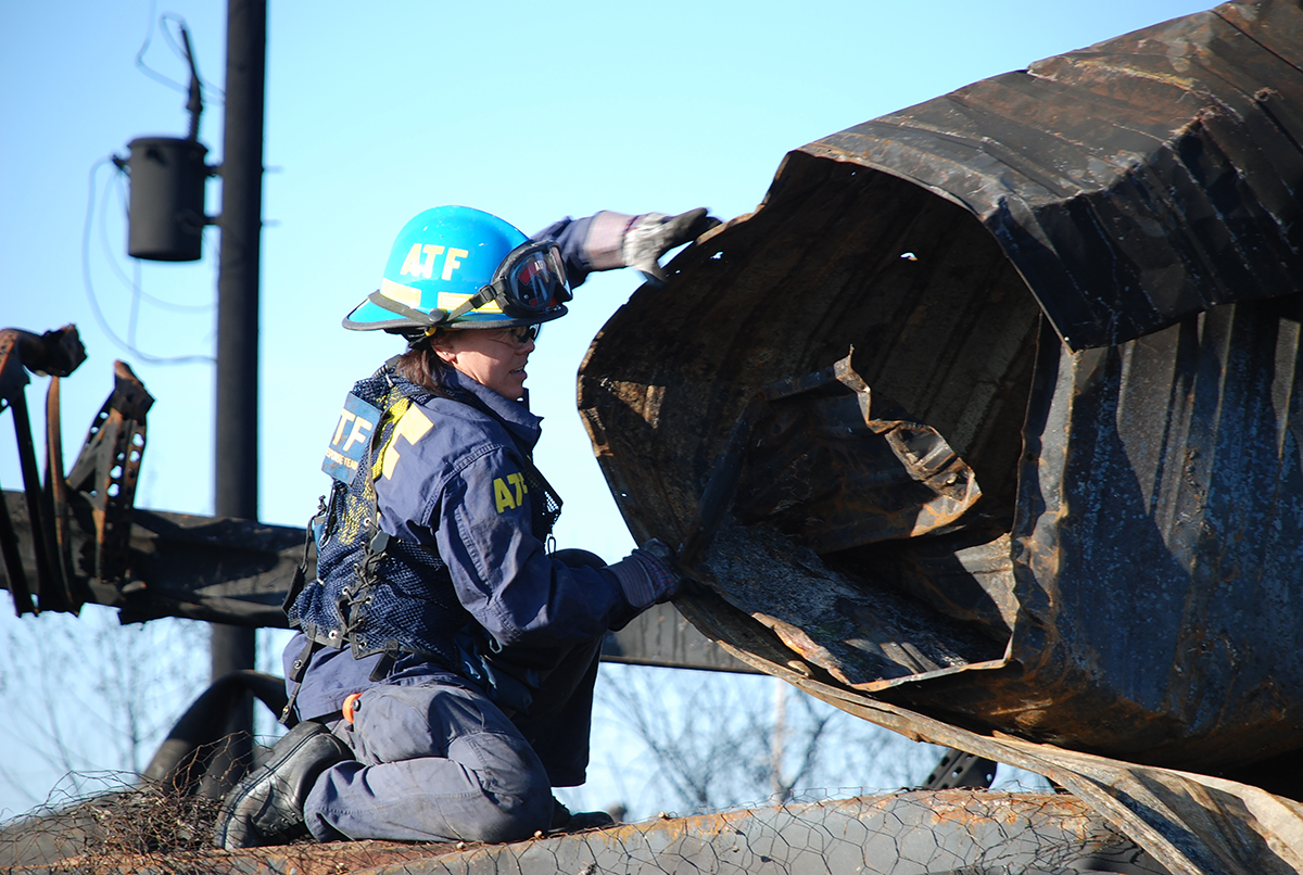 SA-CFI Cindy Chang removes a damaged roof from the Sunbelt Spa crime scene in Texas