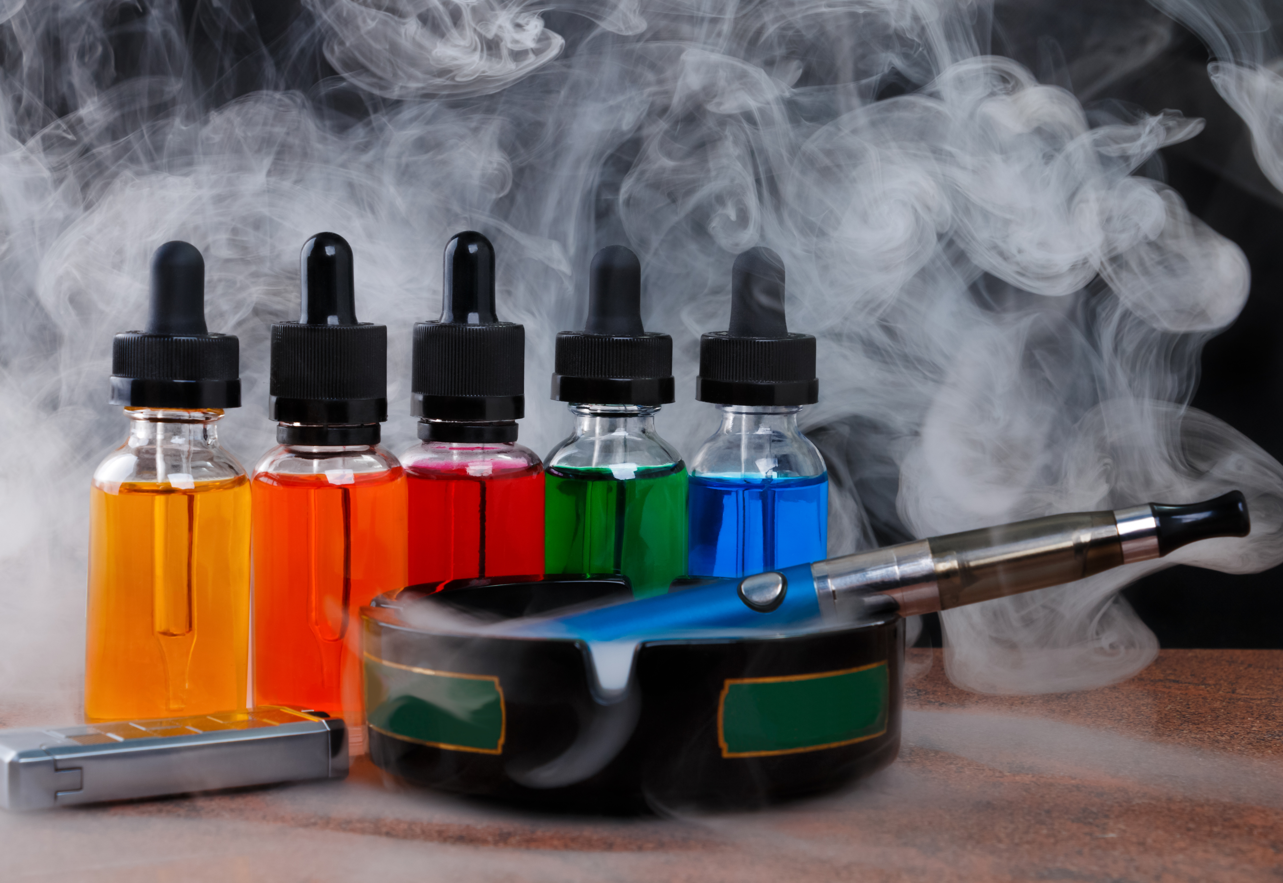 A few bottles of flavored liquid tobacco with an ashtray