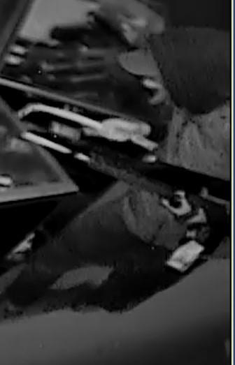 Suspect in Dunham's Sports burglary holding a crowbar and stolen firearm