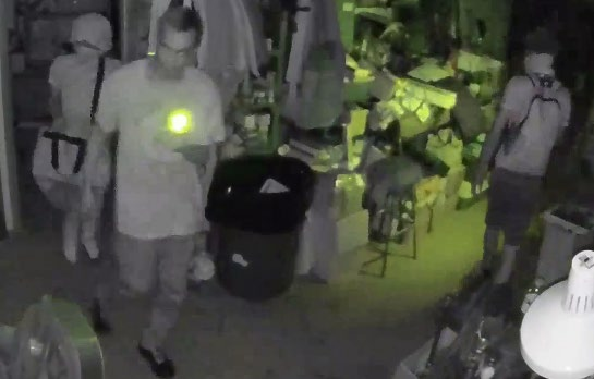 Surveillance image of three individuals with masks on inside Panther City Firearms.