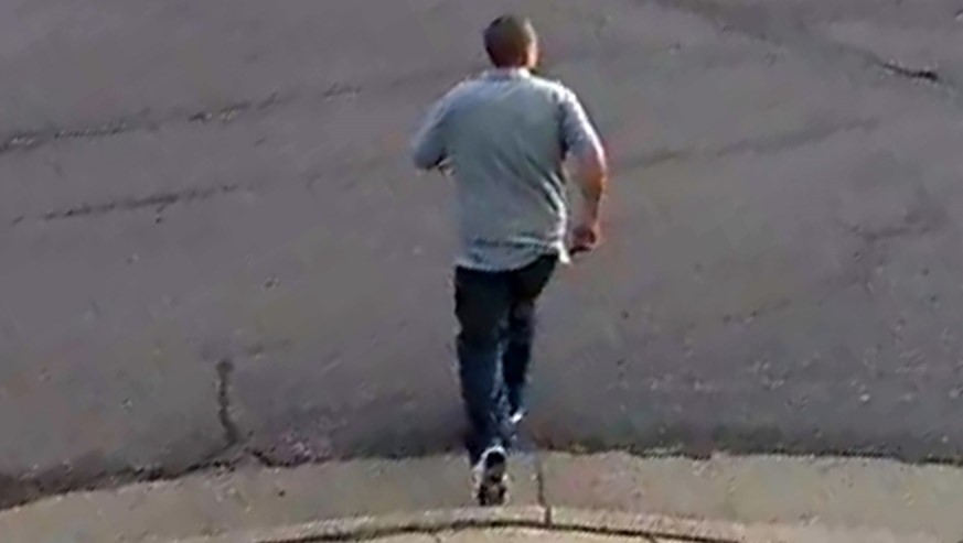 Back view of male suspect in gray polo shirt, dark pants and white shoes