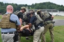 Image of law enforcement carrying team members during training.