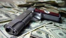 Firearm siting on top of a pile of money.
