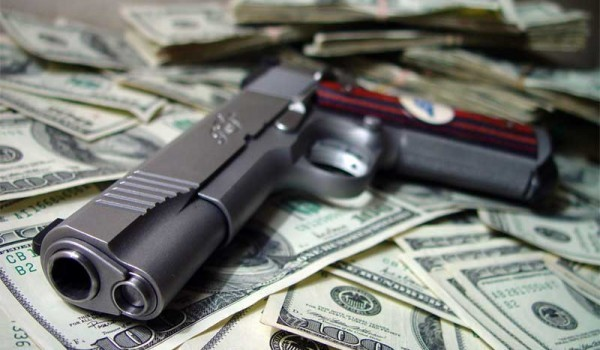 Firearm siting on top of a pile of money